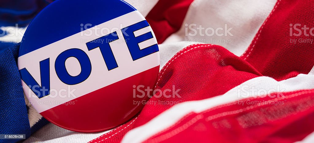 'VOTE' button or pin on an American flag stock photo