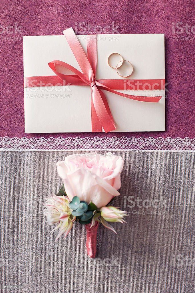 buttonhole of the groom and wedding invitation. Pink color stock photo