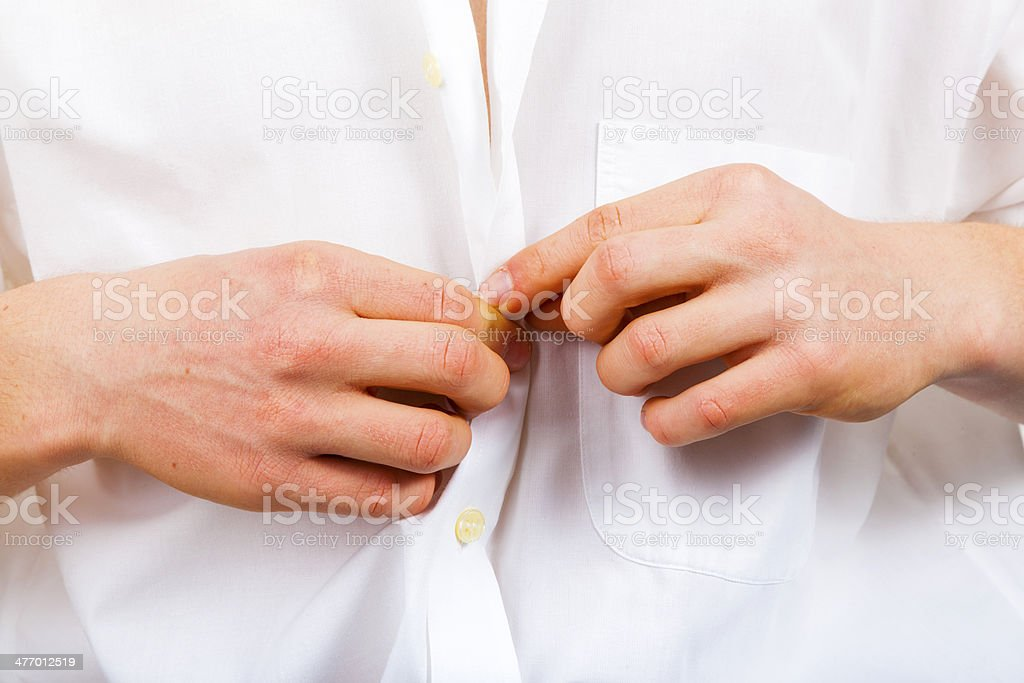 buttoning a fresh, white shirt, on plain white background stock photo