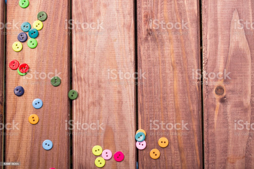 buttons scattered on a brown wooden table stock photo