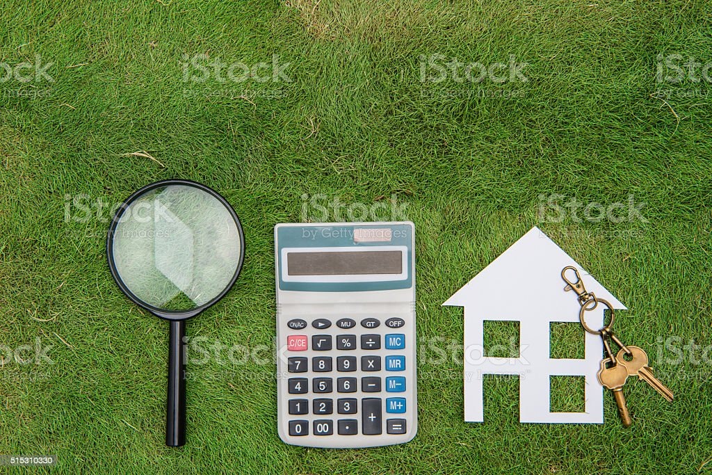 buy green building house Mortgage calculations,  calculator with Magnifier stock photo