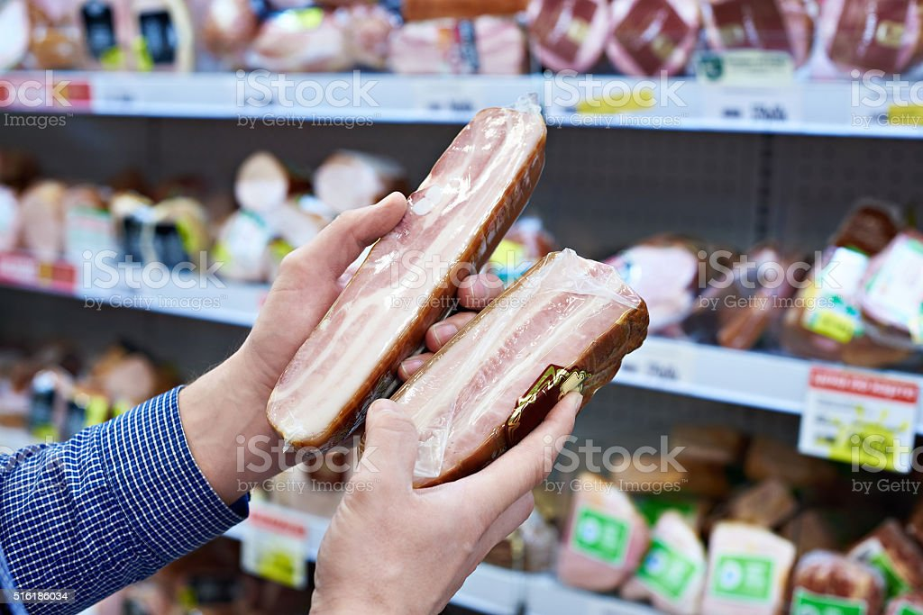 Buyer chooses cooked ham in shop stock photo