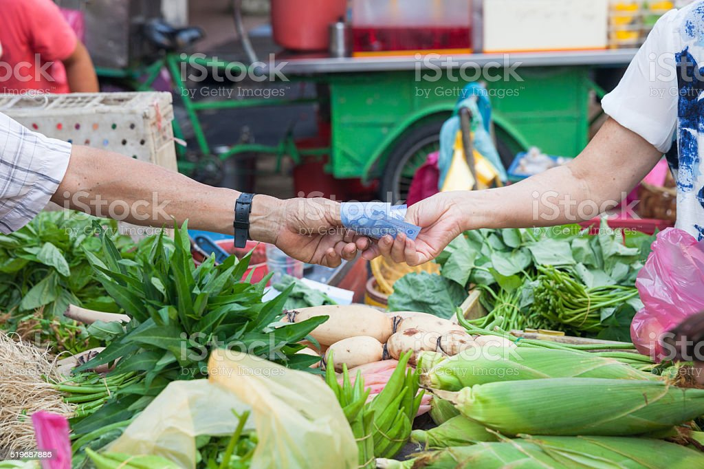 Buyer pays for purchases at the street market stock photo