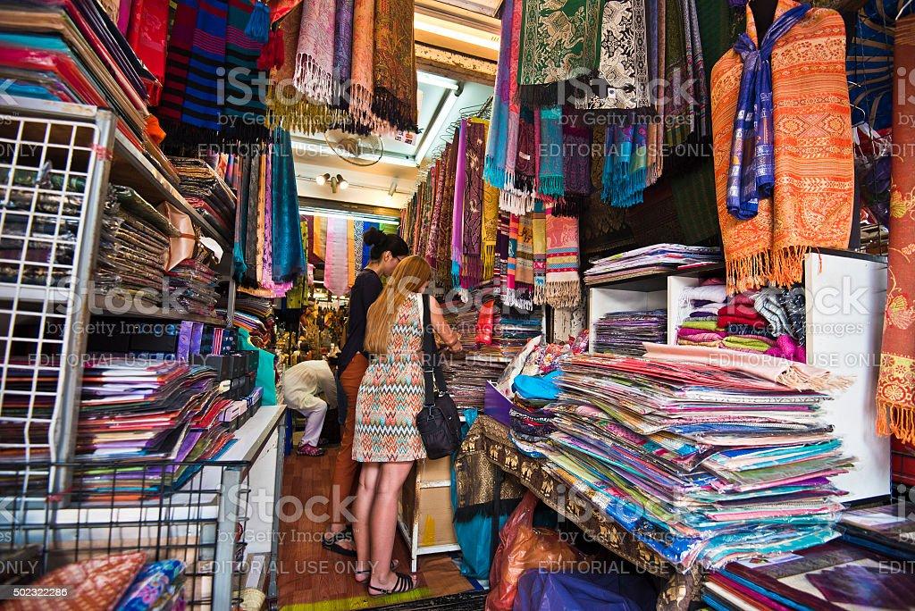 Buying a scarf from pashmina or silk in Bangkok market stock photo