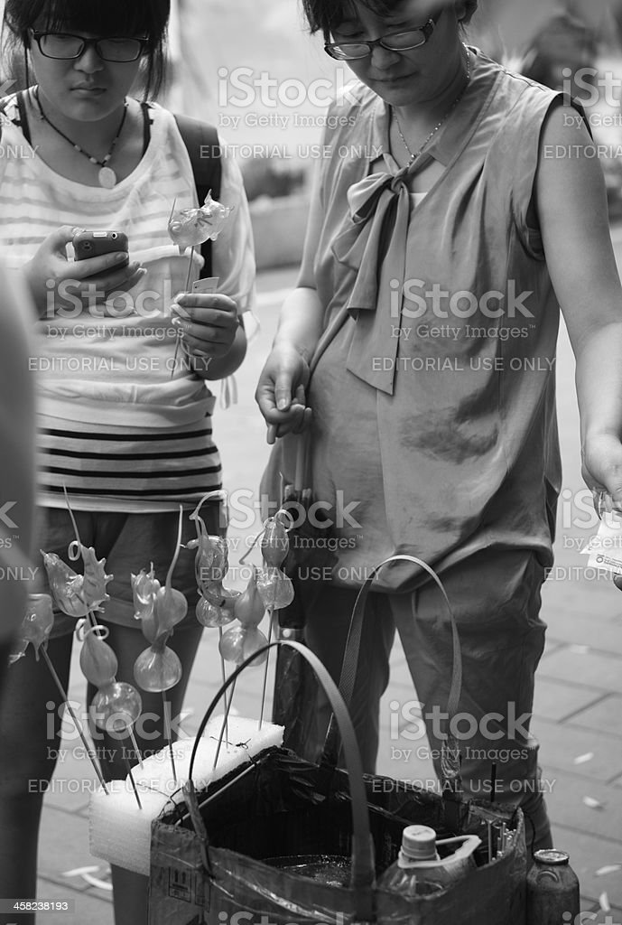 Buying candy figurine from vendor in Beijing street stock photo