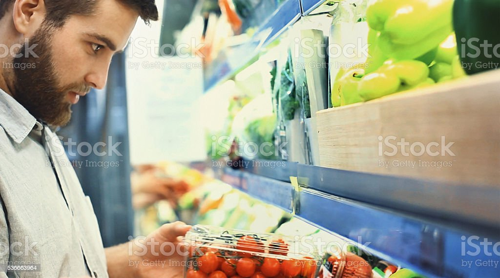 Buying vegetables in supermarket. stock photo