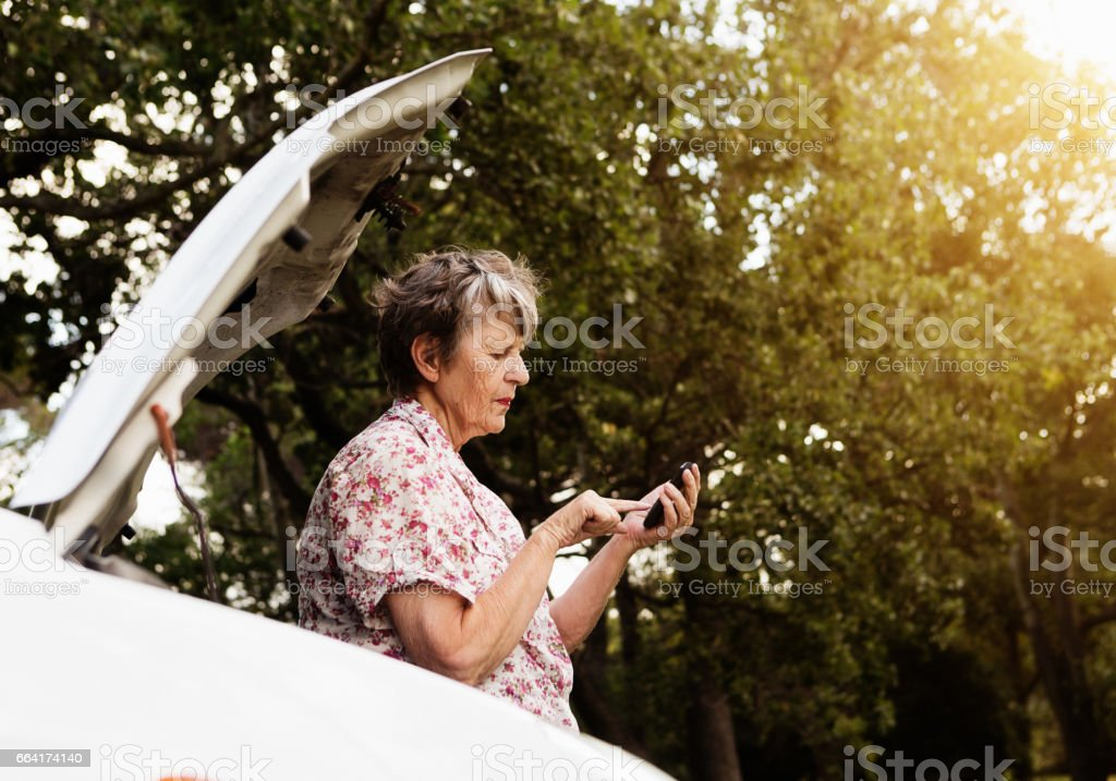 By her broken-down car, an old woman texts for assistance stock photo