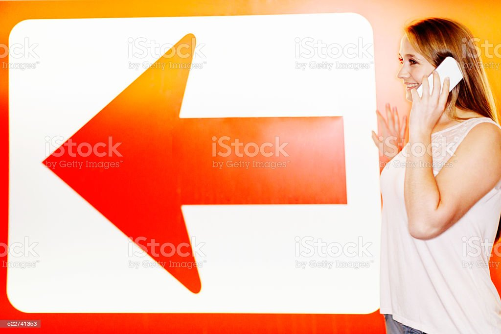 By huge one-way arrow, young woman chats on  mobile phone stock photo