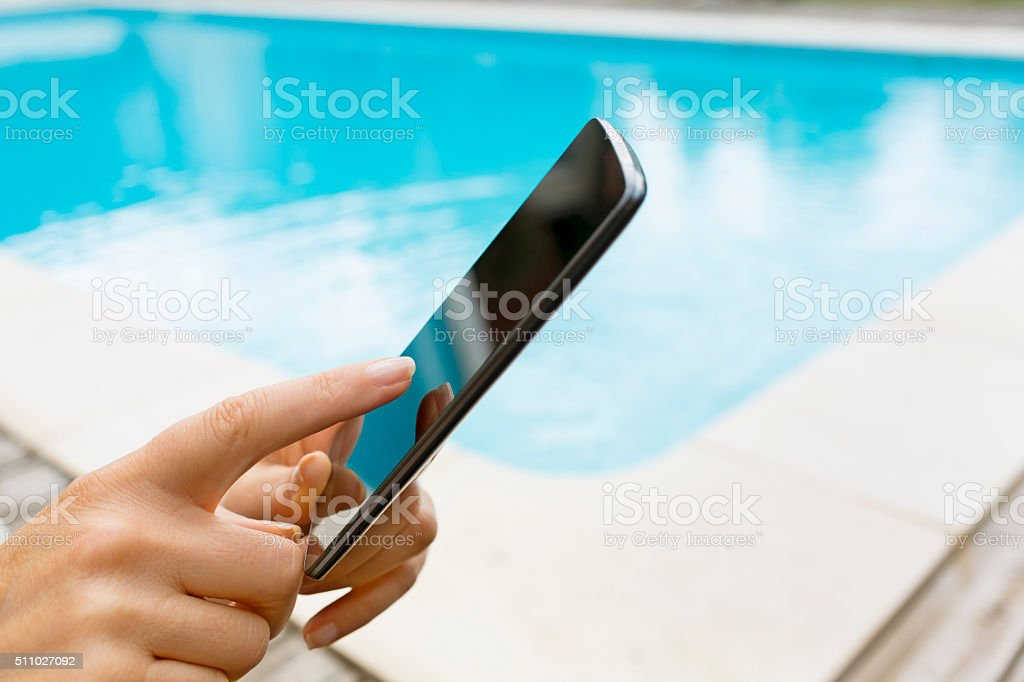 By the pool a woman using her mobile phone stock photo