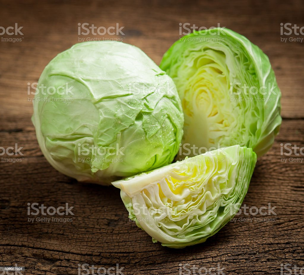 cabbage and cutted cabbage on wooden stock photo