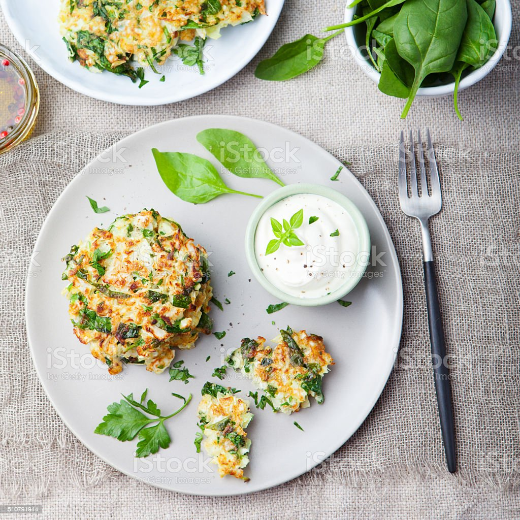 Cabbage and spinach pancakes with yogurt dressing Top view stock photo