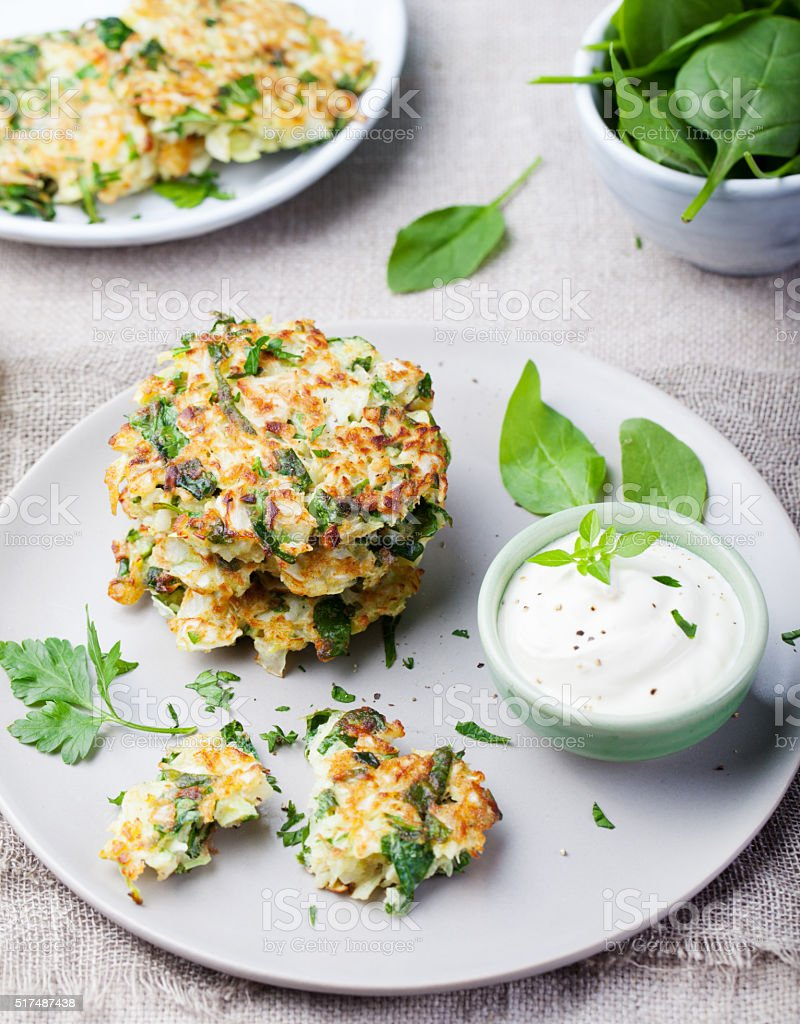 Cabbage and spinach pancakes with yogurt dressing with fresh herbs stock photo