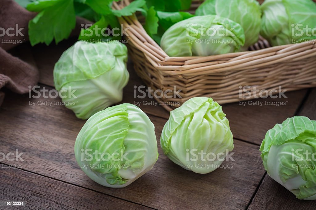 Cabbage on wooden table and basket stock photo