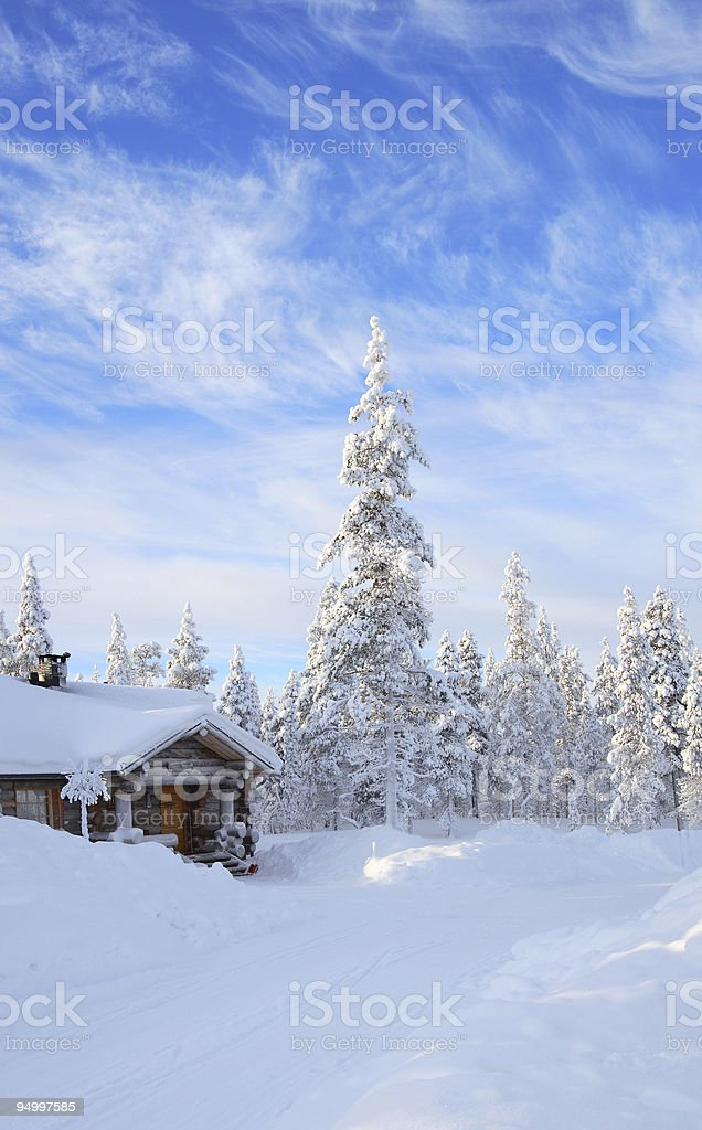 A cabin in the forest covered in snow  stock photo