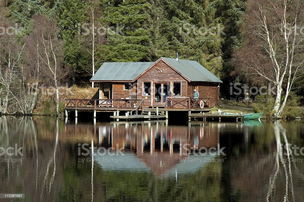 Cabin in the middle of a clear lake royalty-free stock photo