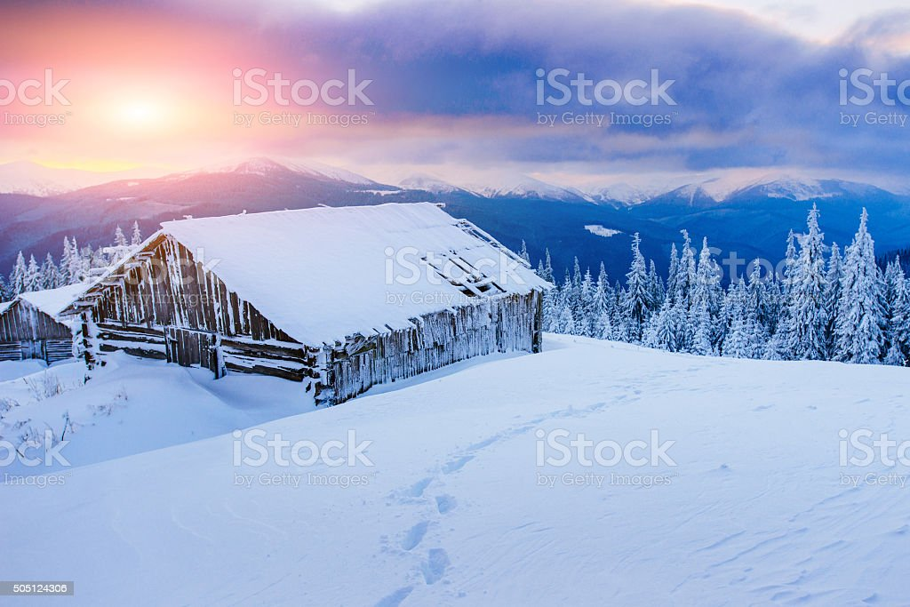cabin in the mountains in winter stock photo
