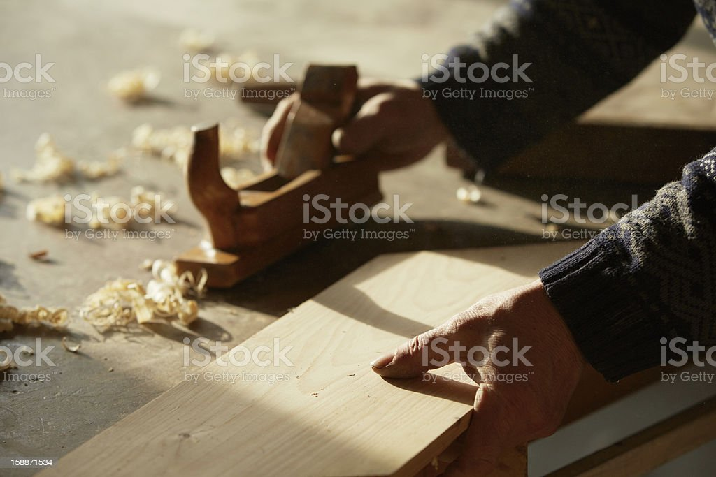 Cabinet makers hands with wood plank and plane royalty-free stock photo