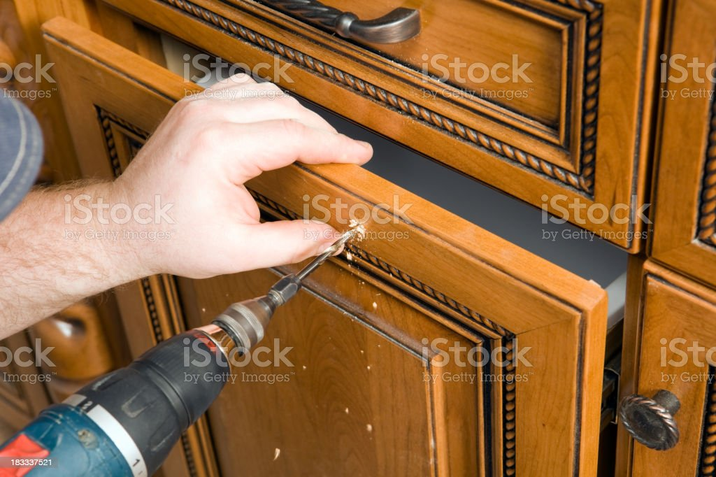 Cabinet Worker Drilling Hole for a new Drawer Pull Handle stock photo