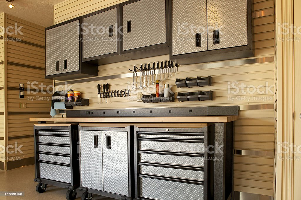 Cabinets and rolling table in garage workspace stock photo