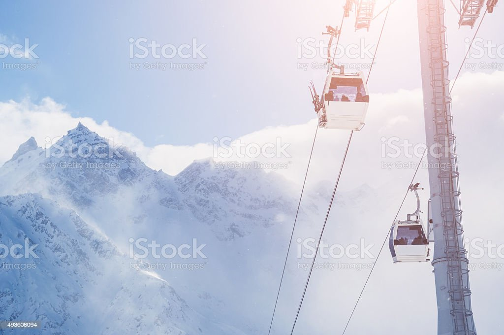 Cable car on the ski resort and snow-covered mountains stock photo