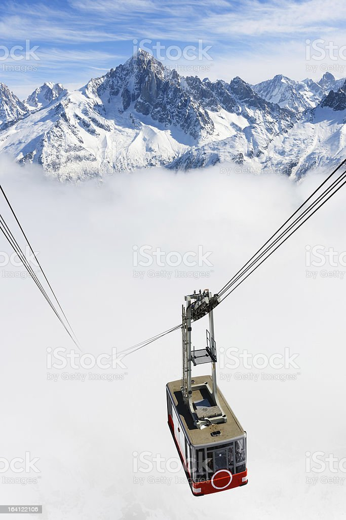 A cable car traveling up a snowy mountain stock photo