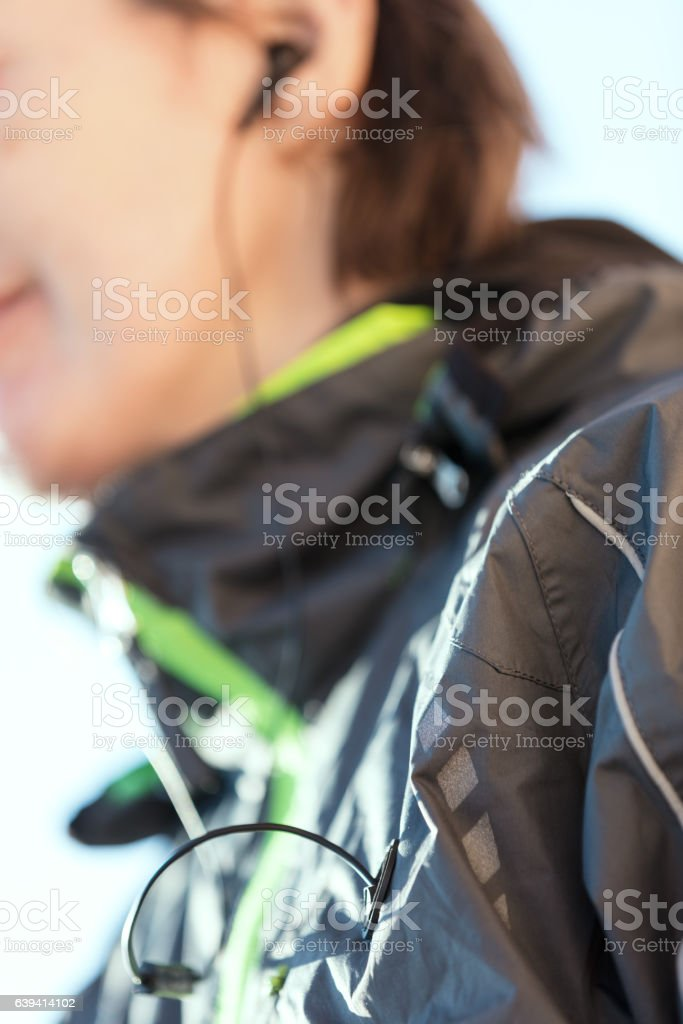 cable of an earphone out of a sport jacket stock photo