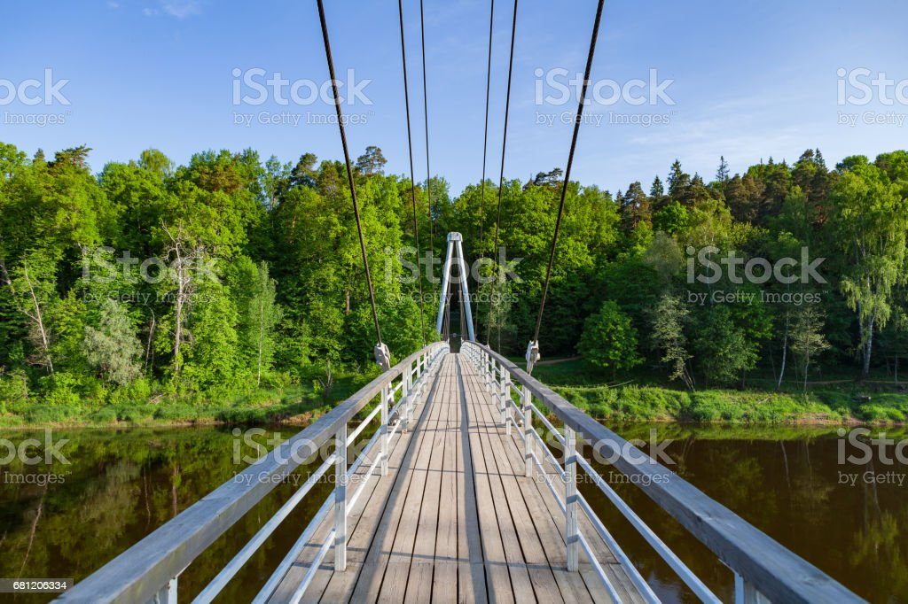 Cable-stayed wooden path bridge over Gauja river with forest at the background stock photo