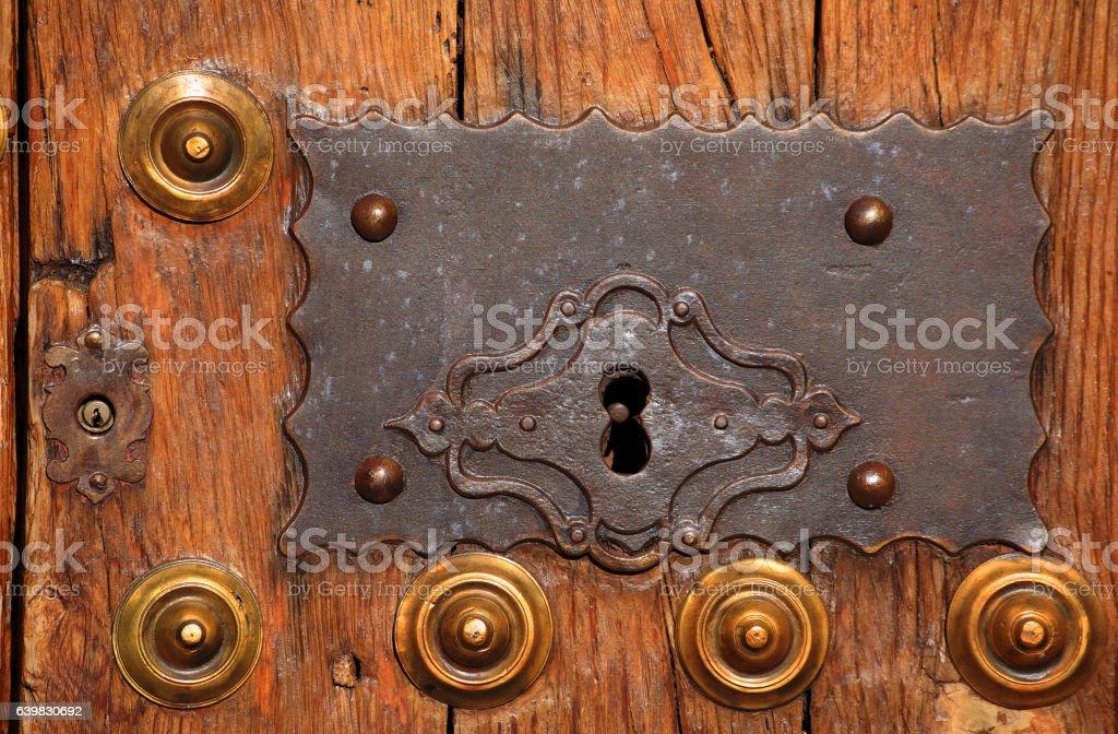 Caceres. Antique oak door with bronze lock and brass studs. stock photo