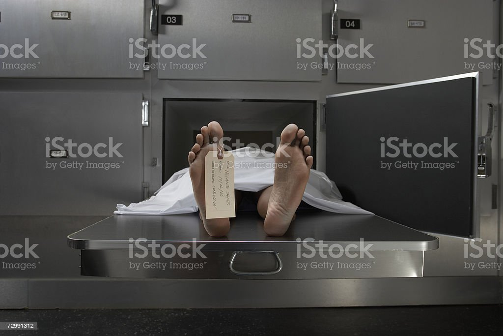 Cadaver on autopsy table, label tied to toe stock photo