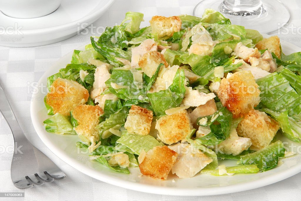Caesar salad served on white plate with silverware stock photo