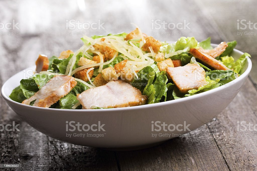 Caesar salad with chicken and greens on a wooden surface stock photo