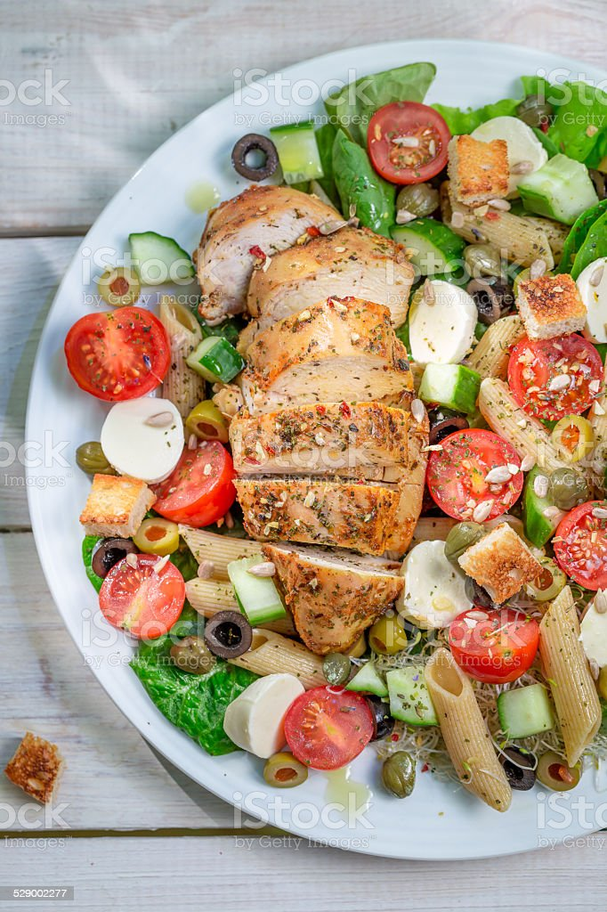 Caesar salad with fresh vegetables and chicken stock photo