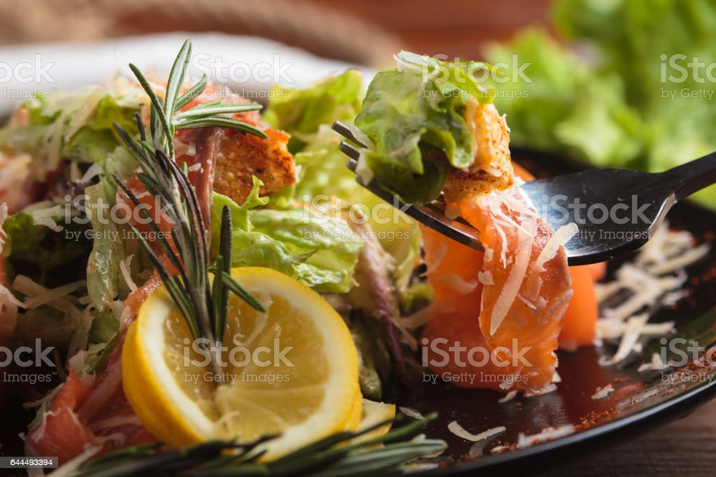 Caesar salad with salmon and cherry tomatoes stock photo