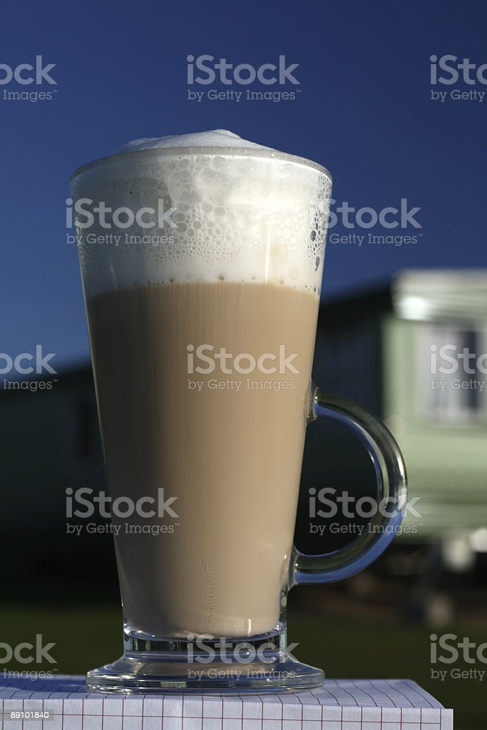 Cafe Latte in a tall glass and deep blue sky royalty-free stock photo