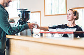 Cafe Owner Handing Customer Drink
