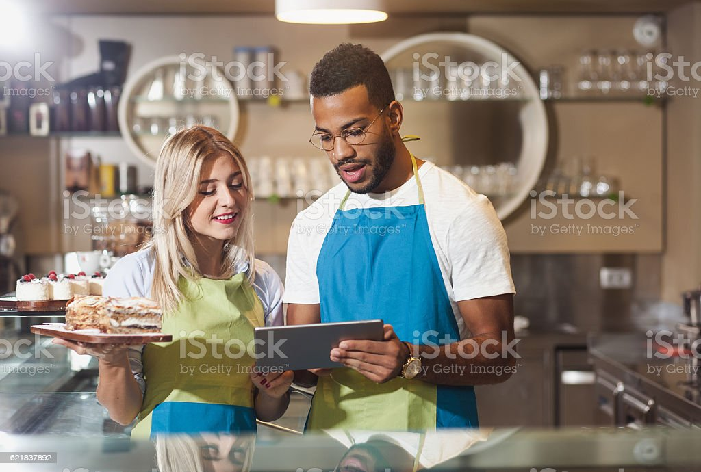 Cafe Owners Discussing and Using a Digital Tablet stock photo