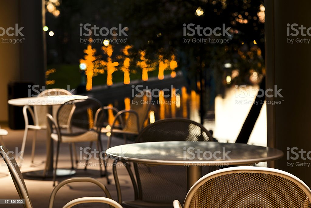 Cafe seating with tranquil water and trees in background royalty-free stock photo