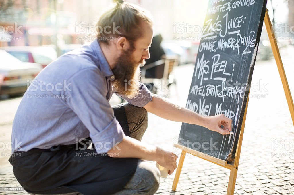 Cafe waiter writing todays special on the board stock photo