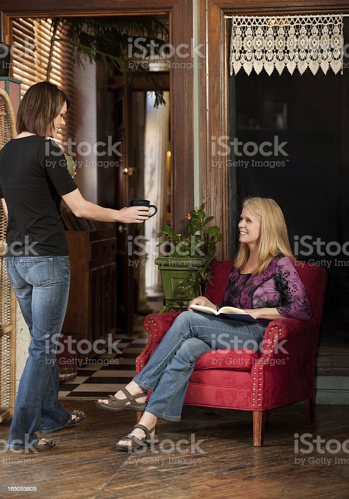 Cafe Waitress Serving Coffee To Senior Woman stock photo