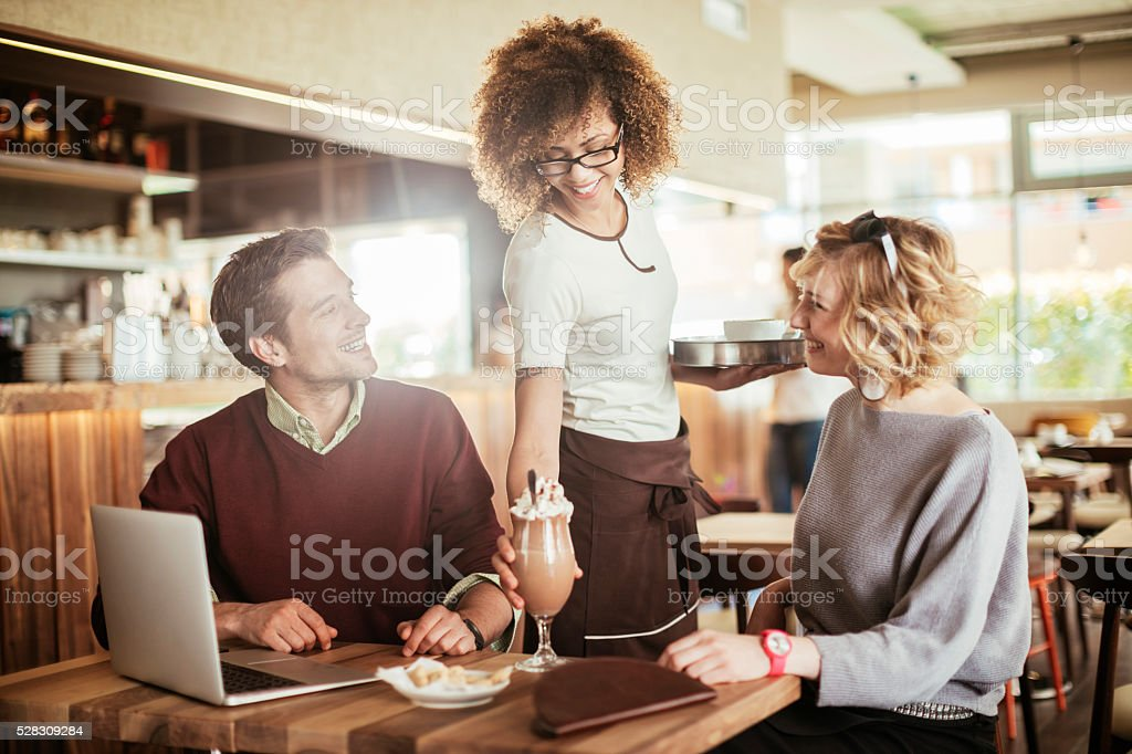 Cafe waitress serving drinks stock photo