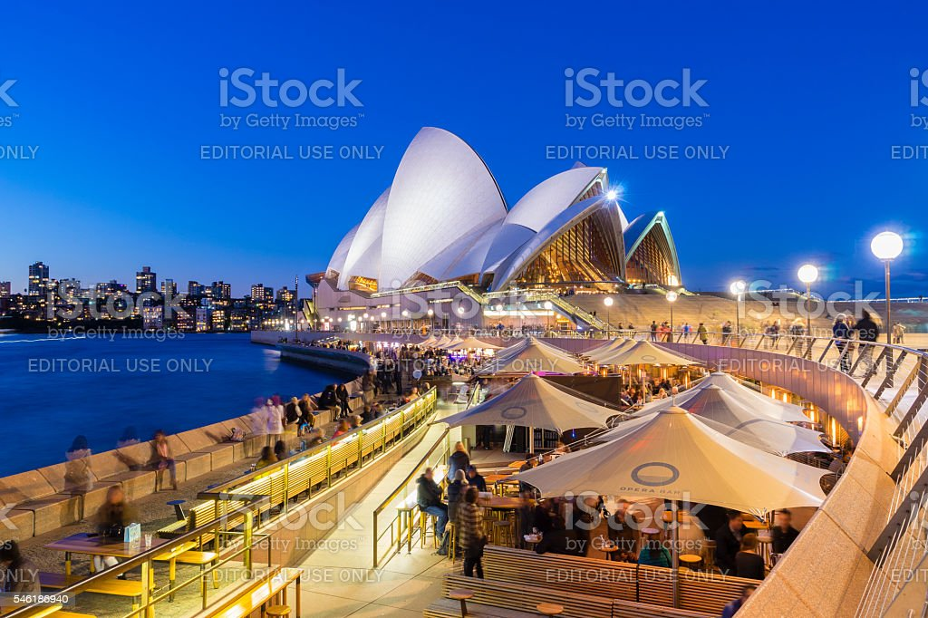 Cafe with people and the Sydney Opera House at twilight stock photo