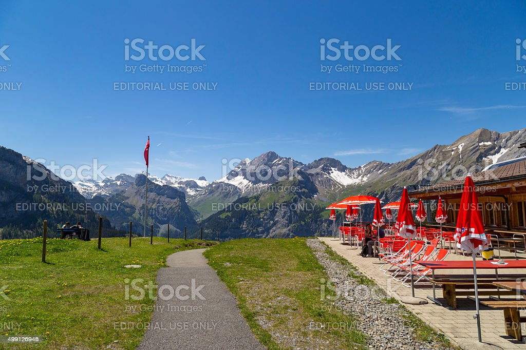 Cafe with red umbrellas in Swiss Alps near Oeschinensee, Switzerland stock photo