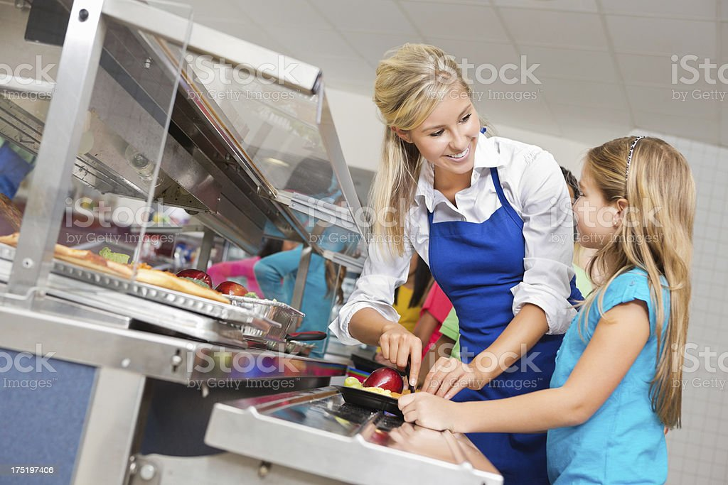 Cafeteria worker helping student choose healthy food in lunch line royalty-free stock photo