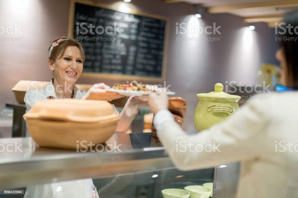Cafeteria worker serving lunch stock photo