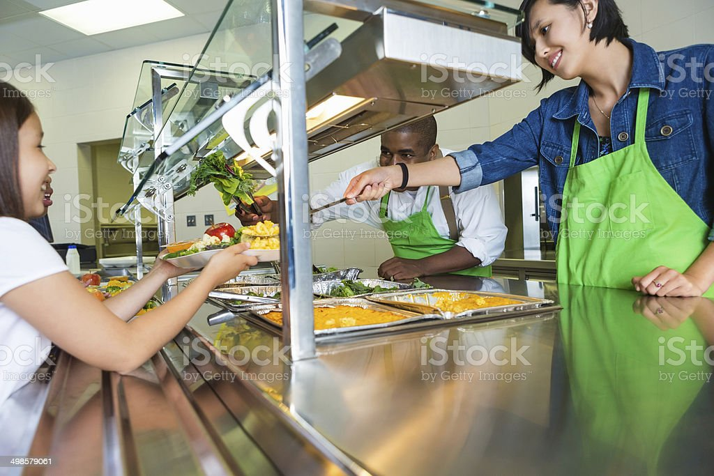 Cafeteria workers serving healthy food options to students in line stock photo