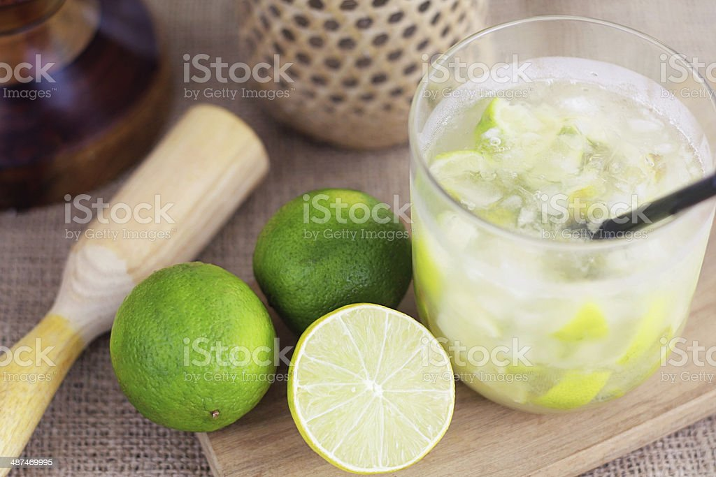 Caipirinha cocktail with limes, pestle and cachaca bottle stock photo