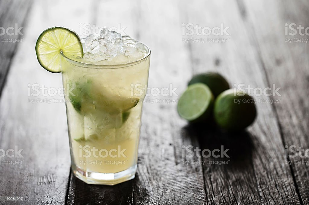 Caipirinha in glass with clicked limes stock photo