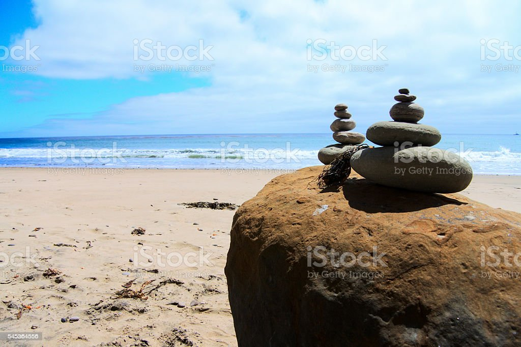 Cairn stones balanced in front of ocean stock photo