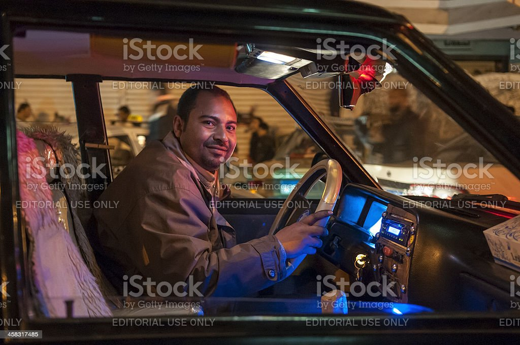 Cairo taxi driver behind wheel at night in Egypt stock photo