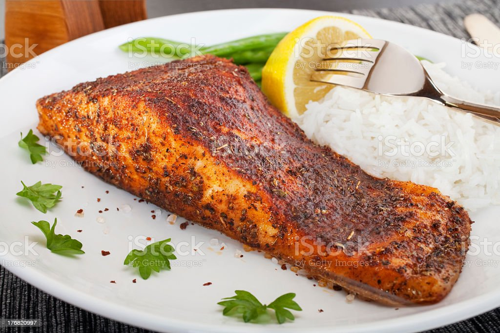 Cajun blackened salmon served with rice and lemon on a plate stock photo
